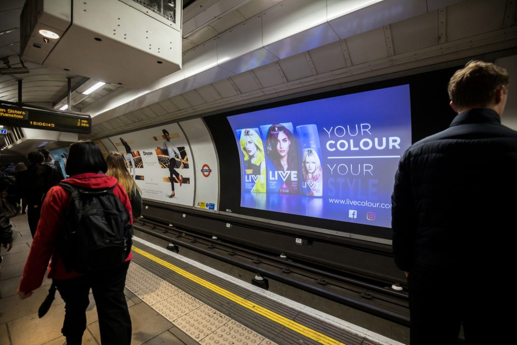 A picture of a London underground platform, showing the DX3 large digital screen across the platform